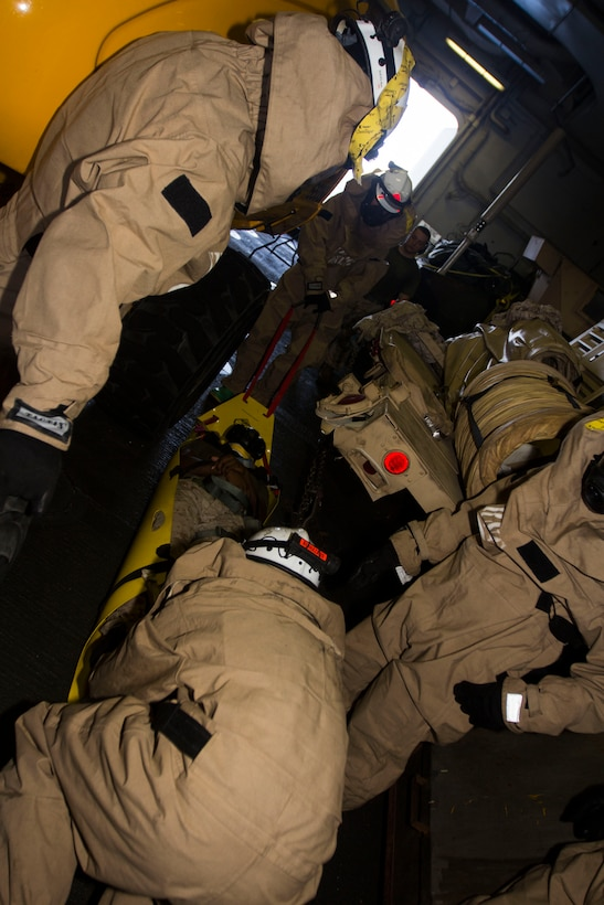 Chemical, biological, radiological and nuclear defense specialist U.S. Marines assigned to the 26th Marine Expeditionary Unit (MEU), transport a simulated casualty on a Skedco during a confined space search and rescue in a hazardous environment exercise, in the hangar bay of the USS Kearsarge (LHD 3), while underway, May 8, 2013. The 26th MEU is deployed to the 5th Fleet area of operations aboard the Kearsarge Amphibious Ready Group. The 26th MEU operates continuously across the globe, providing the president and unified combatant commanders with a forward-deployed, sea-based quick reaction force. The MEU is a Marine Air-Ground Task Force capable of conducting amphibious operations, crisis response and limited contingency operations. (U.S. Marine Corps photograph by Cpl. Kyle N. Runnels/Released)