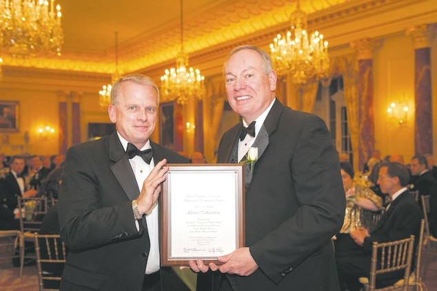 Michael T. Madden, right, receives a Certificate of Honor from Eric Coulter, treasurer, Senior Executive Association's Board of Directors, at the 28th annual black tie Distinguished Rank Awards Banquet held at the State Department Diplomatic Reception Rooms in Washington D.C., April 25.
