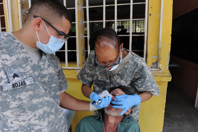 U.S. Army Sgt. Anthony Rojas, Joint Task Force-Bravo Operating Room Technician assist U.S. Army Maj. Perdita Fisher, Joint Task Force-Bravo Dentist, in a tooth extraction during a Medical Readiness exercise, May 6. Joint Task force-Bravo partnered with Honduran Ministry of Health and Honduran military personnel, to provide medical services to more than 500 Cuesta de la Virgen community members. (Photo by Martin Chahin)
