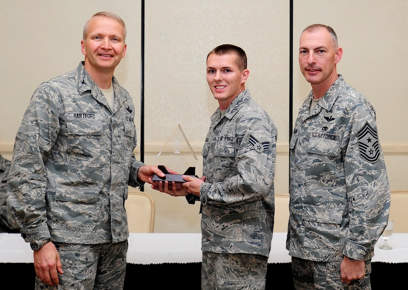 Col. Darren Hartford, 437th Airlift Wing commander, and Chief Master Sgt. Larry Williams, 437th AW command chief, congratulate Senior Airman Brian Hadraba, 437th Maintenance Squadron crew chief, as a Diamond Sharp award winner during a ceremony May 7, 2013, at the Charleston Club at Joint Base Charleston - Air Base, S.C. Diamond Sharp awardees are Airmen chosen by their first sergeants for their excellent performance. (U.S. Air Force photo/Staff Sgt. Rasheen Douglas)