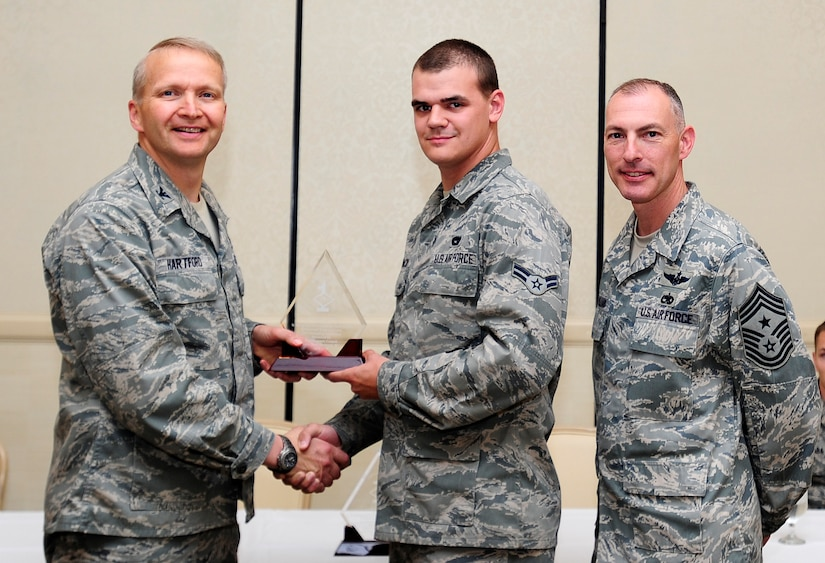 Col. Darren Hartford, 437th Airlift Wing commander, and Chief Master Sgt. Larry Williams, 437th AW command chief, congratulate Airman 1st Class John Mackey, 437th Aerial Port Squadron air transportation apprentice, as a Diamond Sharp award winner during a ceremony May 7, 2013, at the Charleston Club at Joint Base Charleston - Air Base, S.C. Diamond Sharp awardees are Airmen chosen by their first sergeants for their excellent performance. (U.S. Air Force photo/Staff Sgt. Rasheen Douglas)