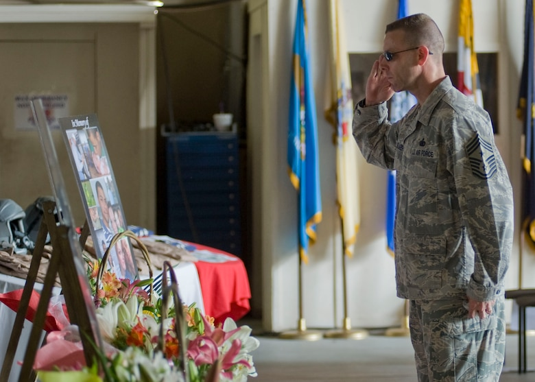 "Chief Master Sgt. Bryan Creager, 376th Air Expeditionary Wing command chief, gives his final salute to the fallen crew members of Shell 77 after a memorial service held in their honor May 9, 2013, at Transit Center at Manas, Kyrgyzstan. Creager, with tear-filled eyes, honored Capt. Mark ""Tyler"" Voss, Capt. Victoria ""Tori"" Pinckney, and Tech. Sgt. Herman ""Tre"" Mackey III, leaving challenge coins to be presented to their families. (U.S. Air Force photo/Staff Sgt. Stephanie Rubi)"