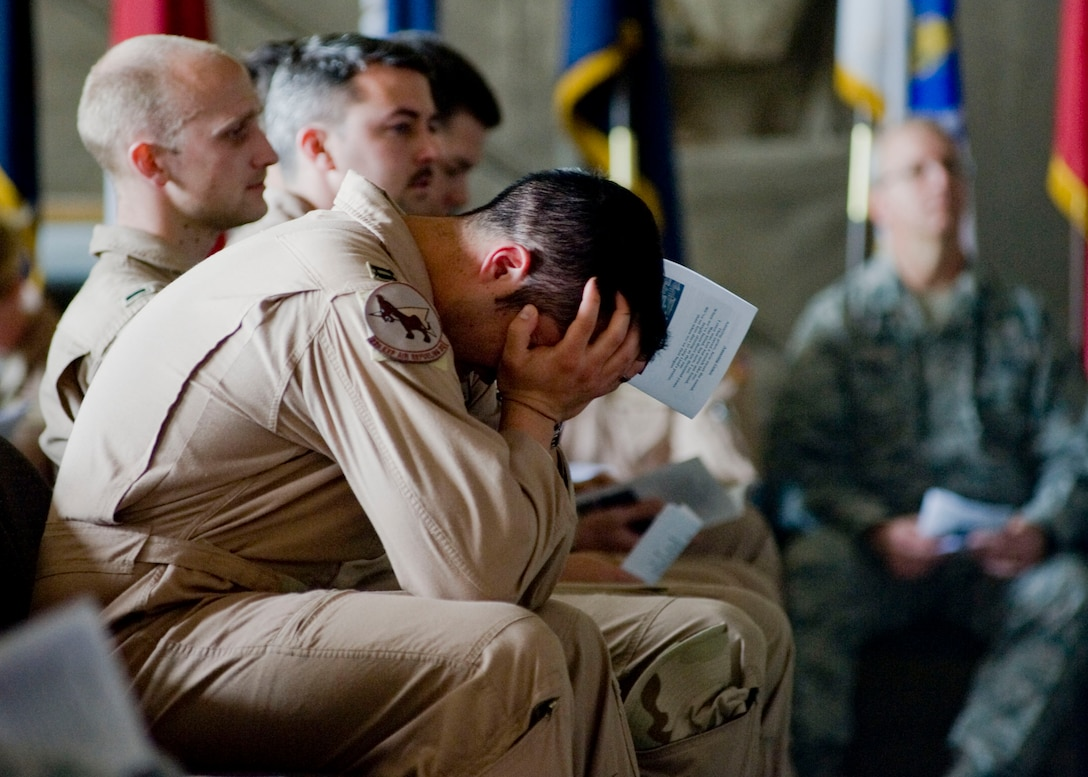 """An Airman mourns during a memorial service May 9, 2013, at Transit Center at Manas, Kyrgyzstan. Service members gathered to honor Capt. Mark """"Tyler"""" Voss, Capt. Victoria """"Tori"""" Pinckney, and Tech. Sgt. Herman """"Tre"""" Mackey III after their aircraft crashed May 3, 2013, in northern Kyrgyzstan. (U.S. Air Force photo/Staff Sgt. Stephanie Rubi)"""