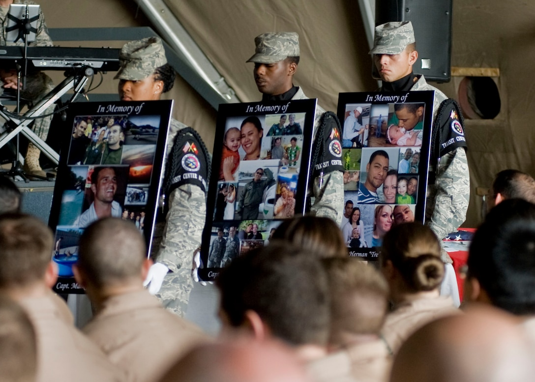 Members from the 376th Air Expeditionary Wing Honor Guard team carry photos of fallen crew members of Shell 77 during a memorial service held in their honor May 9, 2013, at Transit Center at Manas, Kyrgyzstan. The three crew members perished May 3, 2013, when their KC-135 Stratotanker crashed in northern Kyrgyzstan. All three were deployed to the 376th AEW's 22nd Expeditionary Air Refueling Squadron from Fairchild Air Force Base, Wash., in support of Operation Enduring Freedom. (U.S. Air Force photo/Staff Sgt. Stephanie Rubi)