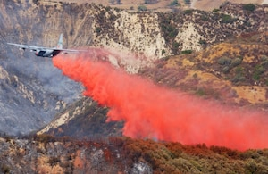 A MAFFS (Modular Airborne Fire Fighting System) equipped C-130E aircraft from the 146th Airlift Wing, Channel Islands Air National Guard Station, makes a Phoschek fire retardant drop on the Simi Fire in Southern California.