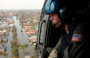 NEW ORLEANS - Coast Guard Petty Officer 2nd Class Shawn Beaty, 29, of Long Island, N.Y., looks for survivors in the wake of Hurricane Katrina Aug. 30.  Beaty is a member of an HH-60 Jayhawk helicopter rescue crew sent from Clearwater, Fla., to assist in search and rescue efforts.  U.S. Coast Guard photograph by Petty Officer 2nd Class NyxoLyno Cangemi