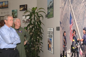 "President George W. Bush and Adm. Timothy J. Keating, commander of U.S. Northern Command, take a moment to reflect at USNORTHCOM's ""9-11 Wall."" The president and Secretary of Homeland Security Michael Chertoff were at USNORTHCOM Sept. 23-24 to monitor Hurricane Rita from the USNORTHCOM Joint Operations Center."