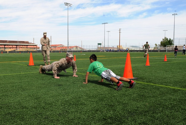 Marine Aircraft Group 13 Marines based at Marine Corps Air Station Yuma, Ariz. volunteered their time for the inaugural Intro to Devil Dogs 101 kid's tour by demonstrating and helping children with the mini-combat fitness course during the mornings events May 8.  The purpose of this event is to increase school-aged childrens' understanding of service in the Marine Corps, build their interest in physical fitness and offer multiple schools a chance to visit the air station prior to the end of the school year.