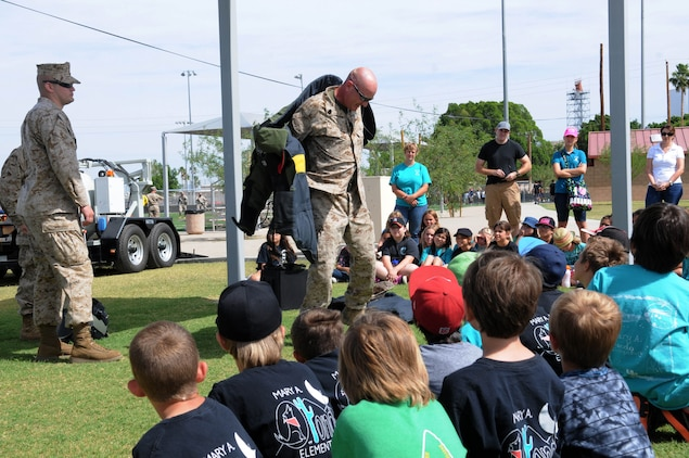 Marines with the explosive ordinance disposal unit for Marine Corps Air Station Yuma demonstrate what kind of work they conduct in the field to the children from local schools taking part in the Intro to Devil Dogs 101 childrens' tour, May 8. Some of the students that attended the Intro to Devil Dogs 101 were military dependents and had a chance to share their parent's military training with fellow classmates.