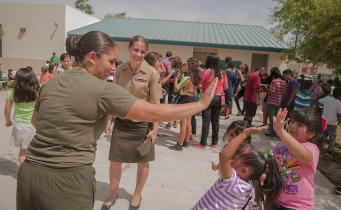 LCpl. Marista Ann Dryden, a Marine Attack Squadron 211 aviation mechanic and a native of Flynt, Mich. (left), and Cpl. Lusetta Elise Lopez, a VMA-211 corrosion control specialist and a native of Spokane, Wash. (right), have a round of high fives with students at George Carver Elementary school after a fun filled day celebration, May 3. The day saw the student body recognize the Marines for their continued and ongoing work with the students and celebrated Cinco De Mayo with performances and traditional music that kept everyone dancing for the duration of the day.