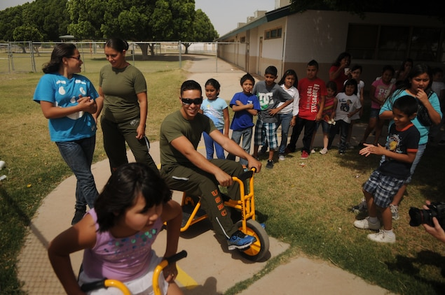 LCpl. Marista Ann Dryden, a Marine Attack Squadron 211 aviation mechanic and a native of Flynt, Mich. (left), and LCpl. Gorge Flores Jr., a VMA-211 egress mechanic and a native of Hamilton, Ohio (right), took part in tricycle races with kids at their squadron's adopted George Carver Elementary school, May 3. The Wake Island Avengers have been building a close relationship with the kids at the schoolhouse in an effort to foster greater relations with the youngest members of the greater Yuma community.