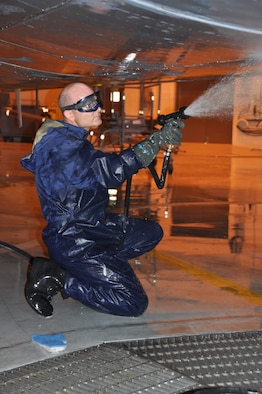 Staff Sgt. Ryan Harris, 507th Aircraft Maintenance Squadron crew chief rinses soap off the belly of a KC-135 Stratotanker which was scheduled for its routine wash on May 5, 2013 in the hanger known as the fuel barn.  Aircraft go through a general wash cycle of 180 days unless they are sent into more corrosive environments.  Depending on the kind of environment the wash cycle changes to either 30, 60 or 120 days.  Flights conducted in salt water areas would be scheduled more often to ensure the salt does not corrode any parts.    Although the aircraft is generally washed with aircraft soap and hot water, some chemicals are authorized for specific needs.  Once the entire aircraft has been thoroughly washed and rinsed, the joints and other parts will get re lubricated and inspected.  This aircraft being washed during the May Unit Training Assembly is good training for traditional reservists.  It not only gives them a chance to perform a through and proper wash along with re lubricating joints and other parts, but also gives them a chance to properly follow instructions from the technical order provided for a proper wash.  (U.S. Air Force photo by Senior Airman Mark Hybers)