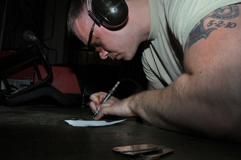 U.S. Air Force Staff Sgt. Michael Durham, 380th Expeditionary Maintenance Squadron Aerospace Ground Equipment production support NCO, uses a pneumatic etcher to engrave tags with identification codes May 8, 2013, here. The tags will be attached to equipment checked out from bench stock and used to ensure accountability by assigning the specific tool code to the Airman who checks out the equipment in the computer-based tool accountability program. Durham is a native of Big Stone Gap, Va., and is deployed from Tinker Air Force Base, Okla. (U.S. Air Force photo by Staff Sgt. Timothy Boyer)