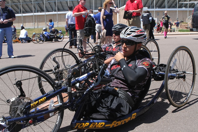Cpl. Marcus Chischilly with Wounded Warrior Battalion West, checks his gear before moving to the starting line of the 10k hand-cycle race during the 2013 Warrior Games at the Air Force Academy. 24-year-old Chischilly from Phoenix, competed in both the hand-cycling and the Marine Corps versus Navy basketball game today. The team of 50 Marines defending champions will compete in several events during the Games including wheelchair basketball, archery, cycling, shooting, sitting volleyball and track and field. They will defend their championship against the Army, Navy, Air Force, Coast Guard, Special Operations Command and the British Armed Forces.