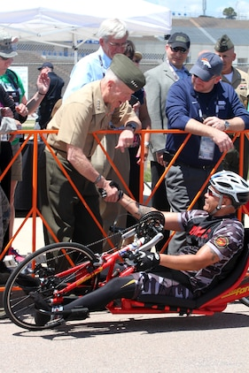 Commandant of the Marine Corps Gen. James F. Amos congratulates Staff Sgt. Ronnie Jimenez, with Wounded Warrior Battalion West, as he finished 10k hand-cycle race during the 2013 Warrior Games at the Air Force Academy. 35-year-old Jimenez from Tempe, Ariz., won the first gold medal in the 2013 Warrior Games setting the Marines on the path to defending their championship. The team of 50 Marines and defending champions will compete in several events during the Games including wheelchair basketball, archery, cycling, shooting, sitting volleyball and track and field. They will defend their championship against the Army, Navy, Air Force, Coast Guard, Special Operations Command and the BritishArmed Forces.