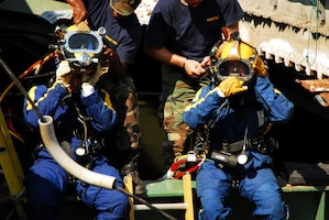 Navy divers from Mobile Dive and Salvage Unit 2 stationed at Naval Amphibious Base Little Creek prepare to enter the water of the I-35 bridge wreckage Aug. 07. When requested by the primary agency and approved by the Secretary of Defense, MDSU 2 may be utilized in support of civil authorities managing disaster recovery efforts.