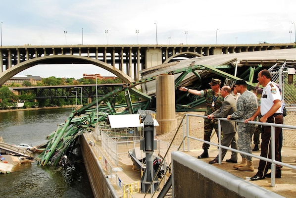 Secretary of the Navy (SECNAV) the Honorable Donald C. Winter, tours the site of the I-35 bridge collapse over the Mississippi river, with Department of Defense, federal, state, and local officials, Aug. 8. Secretary Winter was briefed on the current situation and the progress of the multi-agency search and recovery effort.