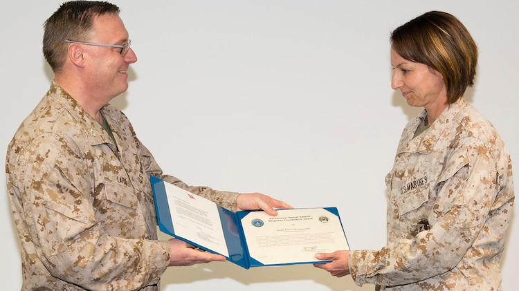 Marine Corps Maj. Robyn Mestemacher, right, accepts her award from Marine Corps Col. Philip Lark, commandant of the Marine Corps chair at the George C. Marshall European Center for Security Studies in Garmisch-Partenkirchen, Germany, on May 10, 2013.