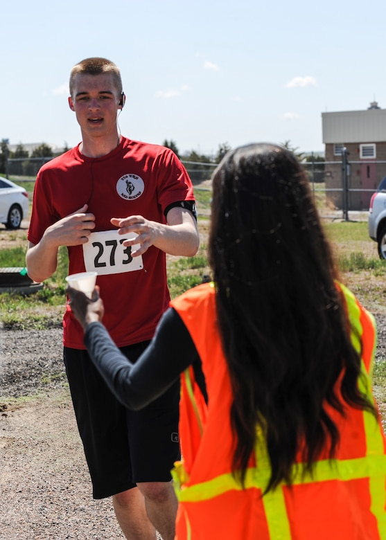 Rick Van Seters, an airman first class with the 460th Space Communications Squadron, takes a cup of water from Andrea McClew, a volunteer, at the last water station during the 7th Annual Buckley Half Marathon May 11, 2013, on Buckley Air Force Base Colo. Van Seters was one of about 50 runners who participated in the 13.1-mile race. (U.S. Air Force photo by Staff Sgt. Christopher Gross/Released)