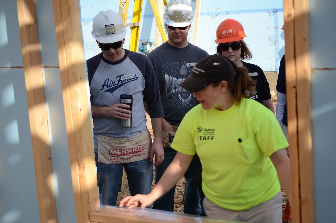 Val Hendricks, Habitat for Humanity staff member, instructs members of Air Force Recruiting Service on how to properly install windows on a home under construction in San Antonio, Texas May 11. Several members of AFRS volunteered their Saturday to assist Habitat for Humanity. The house is scheduled for completion in August. Habitat for Humanity seeks volunteers to help build and landscape affordable homes for qualified low-income families. (U.S. Air Force photo/Staff Sgt. Hillary Stonemetz)