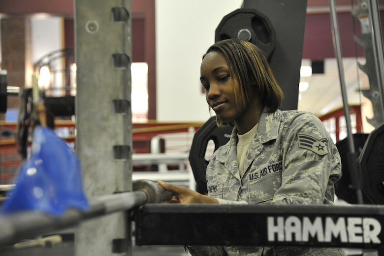 Senior Airman Melissa Givens, 509th Force Support Squadron fitness specialist, adjusts a squat bar at the fitness center on Whiteman Air Force Base, April 22, 2013. Taking care of equipment and maintaining the facility is a daily task each Airmen in the facility must accomplish in order to uphold Whiteman standards. (U.S. Air Force photo by Airman 1st Class Keenan Berry/Released)