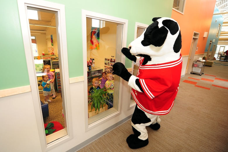 The Chick-fil-A mascot walks down the Child Daycare Center hallway to greet children as part of a Daycare Provider Day donation of 154 prepared lunches to be given to the daycare staff members on May 8 at Offutt Air Force Base, Neb.  The meals included a sandwich, chips, cookie and a choice of sweet or unsweetened tea.  (U.S. Air Force photo by Josh Plueger/Released)