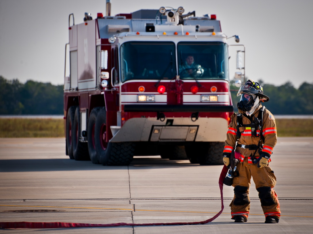 An Eglin Air Force Base firefighter stands by to engage the fire from an F-35 Lightning II during a major accident response exercise May 9.  This was the first MARE involving the Air Force's newest fighter aircraft at Eglin.  First responders had to put out fires on debris from the aircraft after a hard landing.  They also had to extract the injured pilot and get him to medical personnel.  (U.S. Air Force photo/Samuel King Jr.)