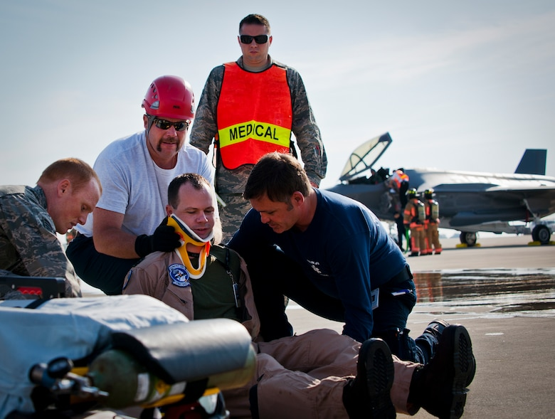 Eglin Air Force Base firefighters and medical technicians prepare to move an injured F-35 Lightning II pilot during a major accident response exercise May 9.  This was the first MARE involving the Air Force's newest fighter aircraft at Eglin.  First responders had to put out fires on debris from the aircraft after a hard landing.  They also had to extract the injured pilot and get him to medical personnel.  (U.S. Air Force photo/Samuel King Jr.)