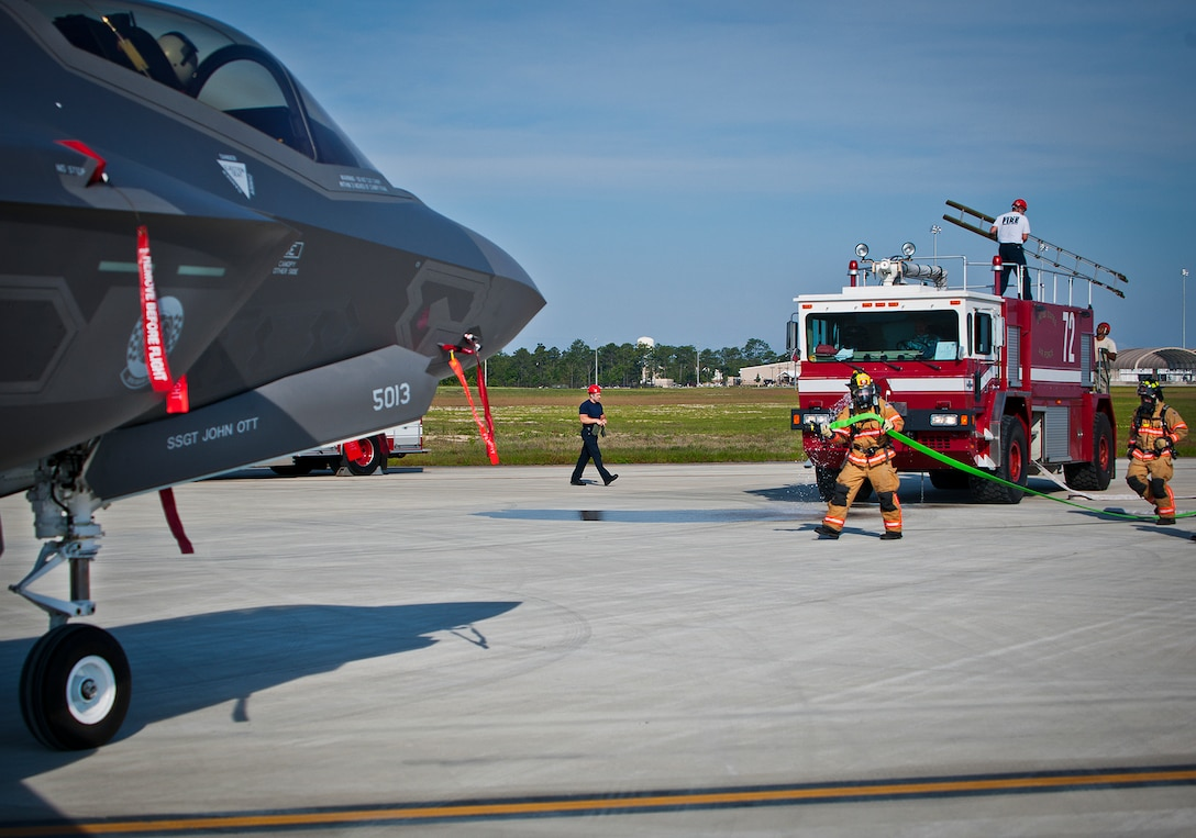 Eglin Air Force Base firefighters move toward a 33rd Fighter Wing F-35 Lightning II during a major accident response exercise May 9.  This was the first MARE involving the Air Force's newest fighter aircraft at Eglin.  First responders had to put out fires on debris from the aircraft after a hard landing.  They also had to extract the injured pilot and get him to medical personnel.  (U.S. Air Force photo/Samuel King Jr.)
