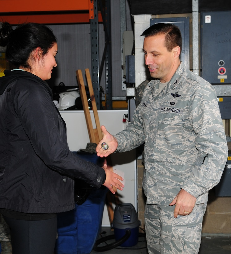 From left, Airman 1st Class Karla Rosas, 100th Security Forces Squadron member from Chicago, receives a commander's coin from Col. Christopher Kulas, 100th Air Refueling Wing commander, May 9, 2013, after she returned home to RAF Mildenhall, England, from a six-month deployment. Rosas was coined by Kulas on behalf of Brig. Gen. Steven Shepro, 438th Air Expeditionary Wing commander, after she won the 438th AEW Airman of the Quarter Award at her deployed location. (U.S. Air Force photo by Karen Abeyasekere/Released)