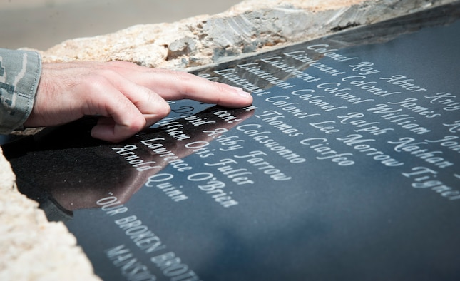 An airman looks through the names of the 22 instructor pilots from the 3645th Pilot Training Squadron, whom were killed in Southeast Asia during the Vietnam War, carved on a memorial at Ribas-Dominicci Circle at Laughlin Air Force Base, Texas, May 8, 2013. A memorial dedication ceremony is scheduled for May 31, 2013. (U.S. Air Force photo/Airman 1st Class John D. Partlow)