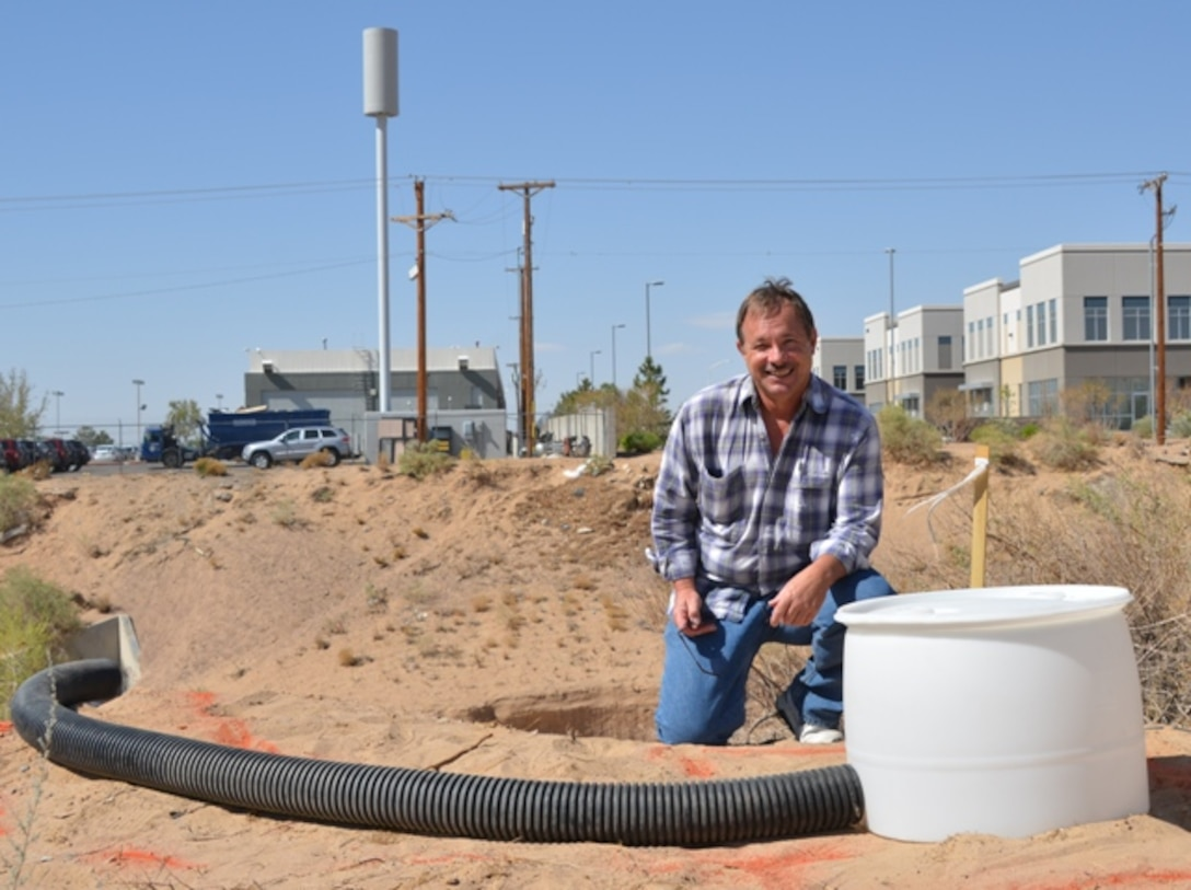 Eddie Paulsgrove, project manager, Regulatory Division, U.S. Army Corps of Engineers, with  the artificial flex pipe and barrel drum owl habitat prior to it being buried.