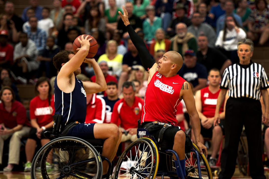 Josue Barron attempts to block a Navy players pass during the first round of the basketball tournament at the 2013 Warrior Games here May 12. The Marines won 53-17. In October 2010, Barron, a native of Cudahy, Calif., was deployed with 3/5, the Darkhorse Battalion. During the deployment, Darkhorse lost 24 men, more than any other Marine unit in Afghanistan in support of operations there. During a patrol, Barron's friend stepped on an improvised explosive device and lost both his legs and a few of his fingers. Barron lost his left leg and left eye. He considers himself lucky. From May 11-16, more than 200 wounded, ill and injured service members and veterans from the U.S. Marines, Army, Air Force and Navy, as well as a team representing U.S. Special Operations Command and an international team representing the United Kingdom, will compete for the gold in track and field, shooting, swimming, cycling, archery, wheelchair basketball and sitting volleyball at the U.S. Olympic Training Center and U.S. Air Force Academy here. The military service with the most medals will win the Chairman's Cup. (U.S. Marine Corps photo by Sgt. Tyler L. Main/Released)