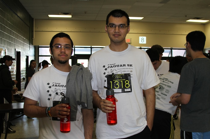 Ameer Khan and Isaiah Abadia hold up their brand new Marine Corps water bottles before the 8th annual Jaguar 5k at Falls Church High School April 27. The Marine Corps donated 900 water bottles to Falls Church High School to support the runners whose race entrance fees went to the athletic department.