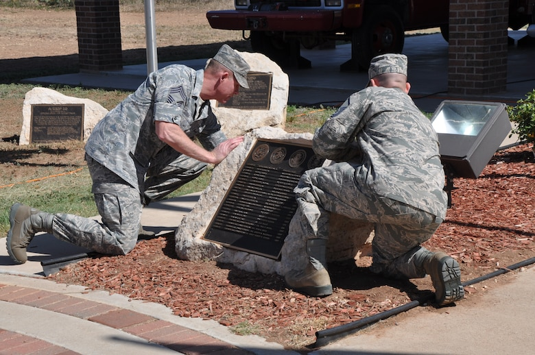 GOODFELLOW AIR FORCE BASE, Texas – Chief Master Sgt. Albert Sisco, 312th Training Squadron superintendent, and Master Sgt. Stephen Thompson, 312th TRS instructor, unveil the fallen Defense Department firefighters' names at a firefighter memorial here, May 3. This year, Goodfellow added seven new names to this memorial rock. (U.S. Air Force photo/ Airman 1st Class Joshua Edwards)