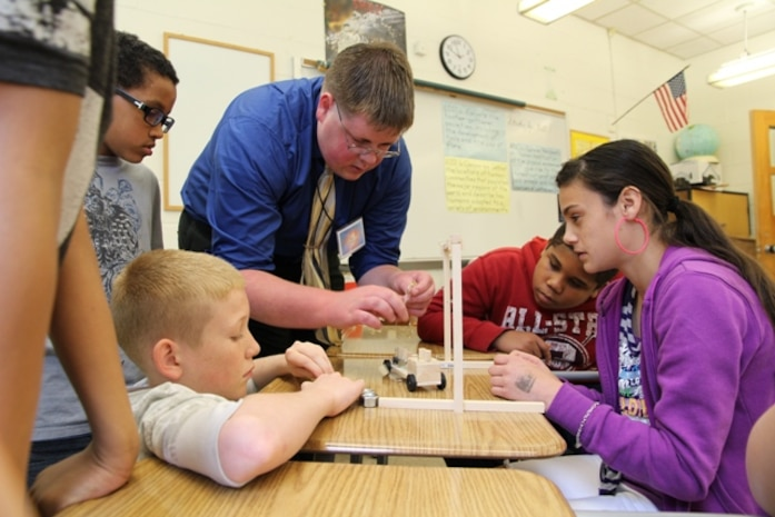 Marine Corps Systems Command engineer Brett Comer helps students prepare sling lengths for his model wooden vehicle during a science, technology, engineering and mathematics, or STEM, event May 9 at Quantico Middle/High School.