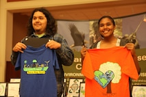 Nicholas Rangel and Alexis May hold t-shirts with their winning designs during the 10th Annual Earth Day Fair and Art Contest at the Marston Pavilion aboard Marine Corps Base Camp Lejeune April 24. The contest received a total of 13 designs. (Photo by Pfc. Justin A. Rodriguez/released)