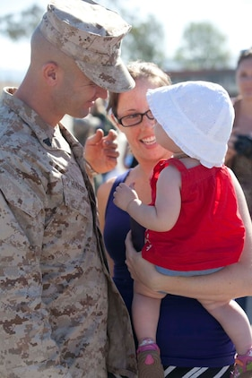 Corporal Jonathan Hunter, an infantryman serving Weapons Company, 3rd Battalion, 5th Marine Regiment, a Dallas native, hugs Joanna, his wife, and their daughter on the parade deck at Camp San Mateo parade deck here, May 13, 2013 Families and friends reunited with their Marines and sailors after an eight-month deployment with the 15th Marine Expeditionary Unit. The MEU deployed Sept 17, 2012, and traveled to Dubai, Jordan, Oman, China, and Hawaii.