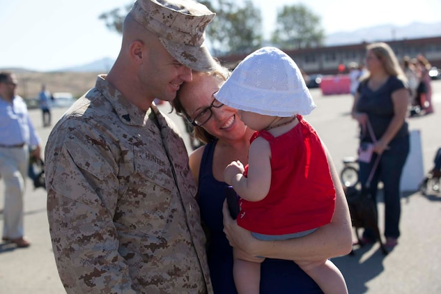 Corporal Jonathan Hunter, an infantryman serving Weapons Company, 3rd Battalion, 5th Marine Regiment, a Dallas native, hugs Joanna, his wife, and their daughter on the parade deck at Camp San Mateo parade deck here, May 13, 2013 Families and friends reunited with their Marines and sailors after an eight-month deployment with the 15th Marine Expeditionary Unit. The MEU deployed Sept 17, 2012, and traveled to Dubai, Jordan, Oman, China, and Hawaii. MARINE CORPS CAMP PENDLETON, Calif., - Corporal Jonathan Hunter, an infantryman serving Weapons Company, 3rd Battalion, 5th Marine Regiment, a Dallas native, hugs Joanna, his wife, and their daughter on the parade deck at Camp San Mateo parade deck here, May 13, 2013 Families and friends reunited with their Marines and sailors after an eight-month deployment with the 15th Marine Expeditionary Unit. The MEU deployed Sept 17, 2012, and traveled to Dubai, Jordan, Oman, China, and Hawaii.