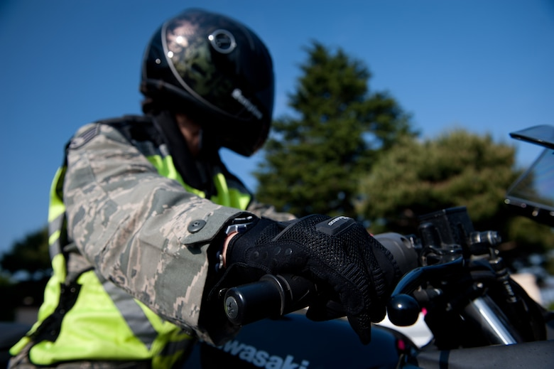 Staff Sgt. Victoria Mani, 6-year motorcycle rider, prepares to ride her motorcycle at Yokota Air Base, Japan, May 15, 2013.  Mani is prepared for a safe ride wearing her Department of Transportation standard helmet, protective clothing and padded full-fingered gloves, sturdy over the ankle footwear and a visible vest.  (U.S. Air Force photo by Senior Airman Cody H. Ramirez/Released)