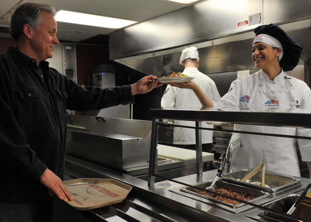 Airman 1st Class Taqla (Tina) Eidson, Force Support Squadron food service specialist, hands a customer breakfast during the Hennessy Evaluation at the Touch N' Go In-Flight Kitchen at Whiteman Air Force Base, Mo., April 3, 2013. Winners must display excellence in management effectiveness, force-readiness support, food quality, employee and customer relations, resource conservation, and training and safety awareness. (U.S. Air Force photo by Heidi Hunt/Released)