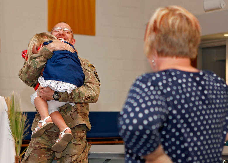 Mrs. Kristie Jarmusz looks on as Maj. Gregory Jarmusz, 412th Security Forces Squadron former operations officer, surprises his daughter during an AWANA (Approved Workman Are Not Ashamed) awards presentation event held at Chapel 2 May 9, 2013. Major Jarmusz returned from a one-year deployment in time to surprise his daughter at the very end of the awards ceremony. (U.S. Air Force photo by Jet Fabara)