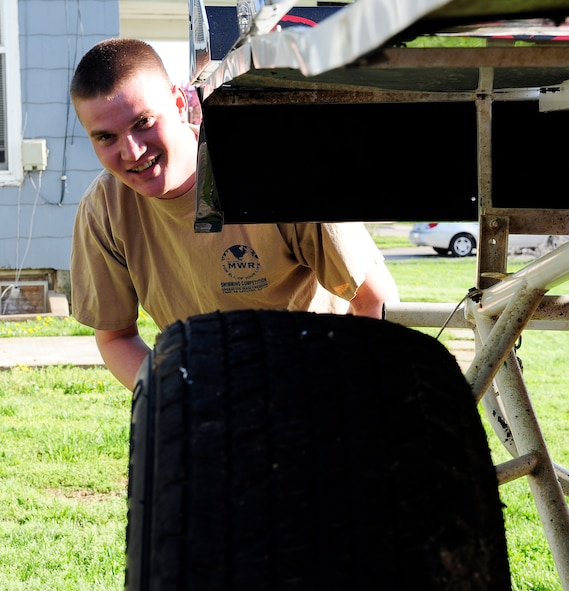 Staff Sgt. Chris Brockway, 442nd Logistics Readiness Squadron traffic management office apprentice, smiles from behind his B-Modified racecar in Warrensburg, Mo., April 29, 2013. Brockway has been racing for almost eight years. (U.S. Air Force photo by Airman 1st Class Shelby R. Orozco/Released)