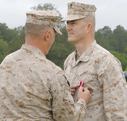 Maj. Kenneth W. Battaglia, Inspector-Instructor, Detachment 2, Supply Company, 4th Supply Battalion, 4th Marine Logistics Group, receives a Meritorious Service Medal from Col. Donald J. Davis, commanding officer, Marine Corps Logistics Base Albany, during a retirement ceremony held at Schmid Field, here, May 4.