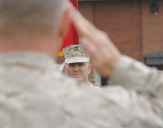 Maj. Kenneth W. Battaglia, Inspector-Instructor, Detachment 2, 4th Marine Logistics Group, salutes Col. Donald J. Davis, commanding officer, Marine Corps Logistics Base Albany, during his retirement ceremony held at Schmid Field, here, May 4.