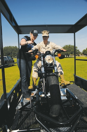 "Maj. Paulina Rojas with Marine Corps Logistics Command learns the basics of a motorcycle during hands-on training at Marine Corps Logistics Command's biannual safety stand-down at the ""101 Critical Days of Summer,"" May 9 at Covella Pond. The event provided details on motorcycle safety, private motor vehicle safety, recreational vehicle safety, boats and watercraft safety, and more to reduce or minimize injuries and/or fatalities."