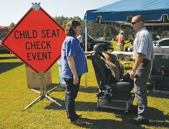 A Georgia State patrolman explains the proper way to use a child safety seat during Marine Corps Logistics Command's biannual safety stand-down that focused on summer safety May 9 at Marine Corps Logistics Base Albany's Covella Pond.