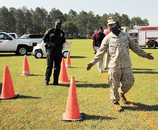 "Sgt. Emal Britt with Marine Corps Logistics Base Albany tries to navigate around cones while wearing goggles that simulate being impaired after drinking alcohol at the ""101 Critical Days of Summer,"" May 9 at Covella Pond."