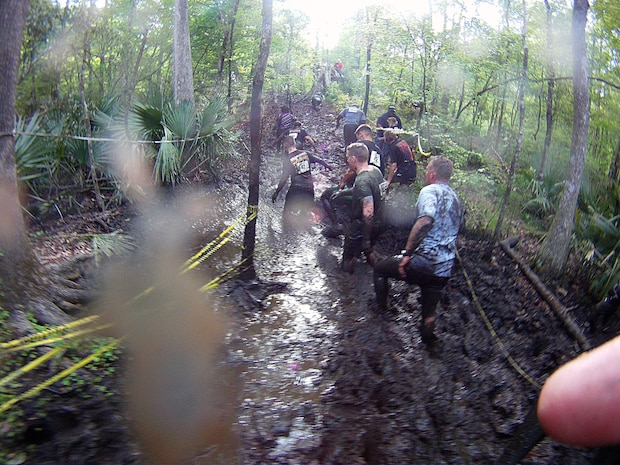"""Participants of the infamous """"Mud, Seat and Tears Run"""" sponsored by U.S. Marine Corps Forces, Special Operations Command, endure an intense trail filled with forest terrain, winding trails, fallen trees and giant mud pits April 27, 2013. The run consisted of a five-mile trek through the woods and muddy terrain of Stone Bay."""