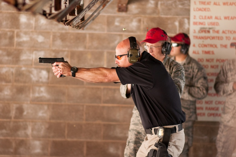 Under the watchful eye of 72nd Security Forces Squadron personnel, FBI Special Agent Doug Frost takes aim at his target during the Air Force Office of Special Investigations Detachment 114 pistol competition May 10. The FBI team took home top honors in the annual competition. (Air Force photos by Chad Jespersen)